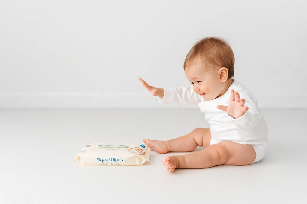 Baby playing with Aqua Wipes pack
