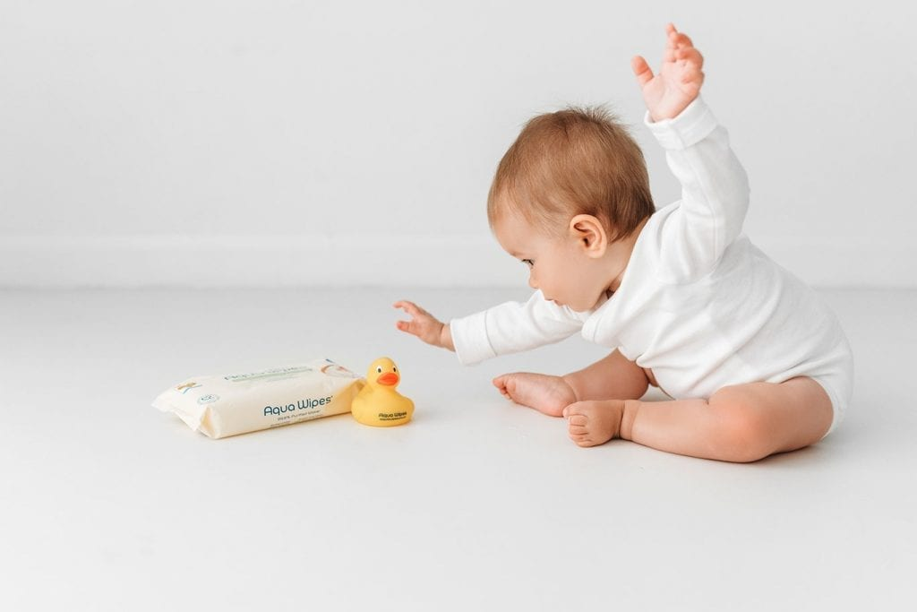 Baby playing with Aqua Wipes pack and toy duck